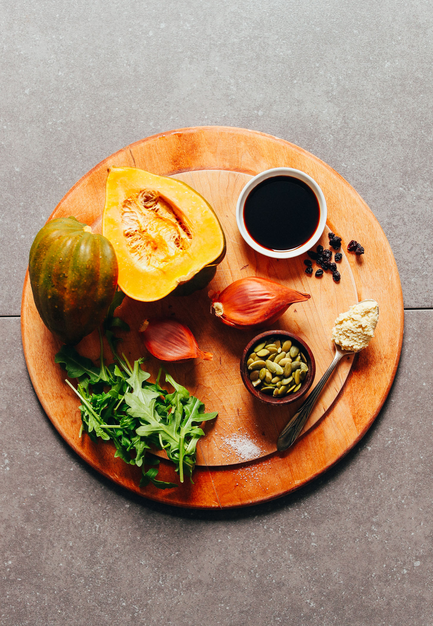 Wood cutting board with acorn squash, shallots and other ingredients for making a delicious plant-based fall salad