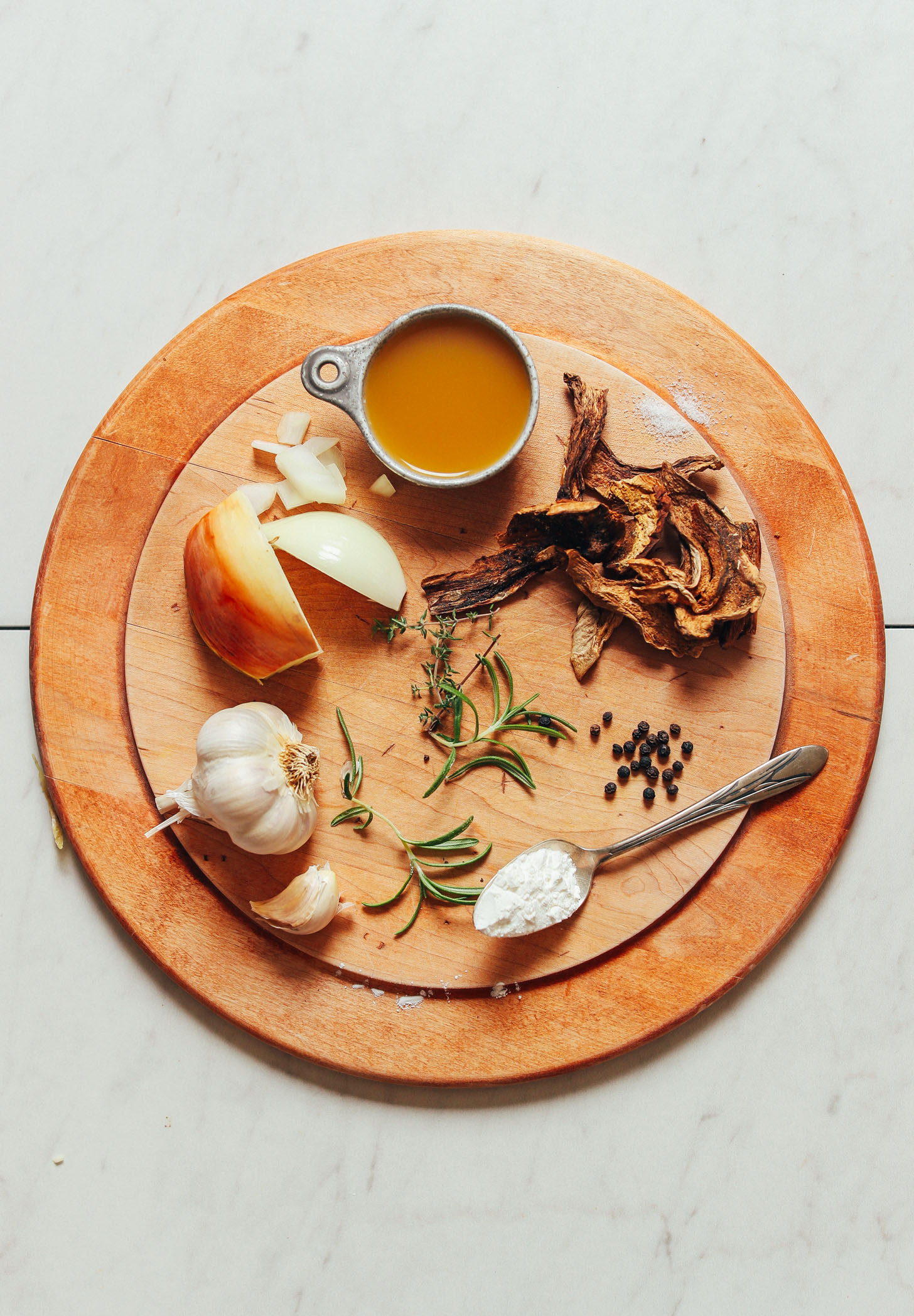 Wood cutting board with ingredients for making our simple homemade vegan gravy recipe