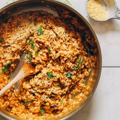 Using a wooden spoon to stir a pan of our delicious Vegan Caramelized Shiitake Mushroom Risotto