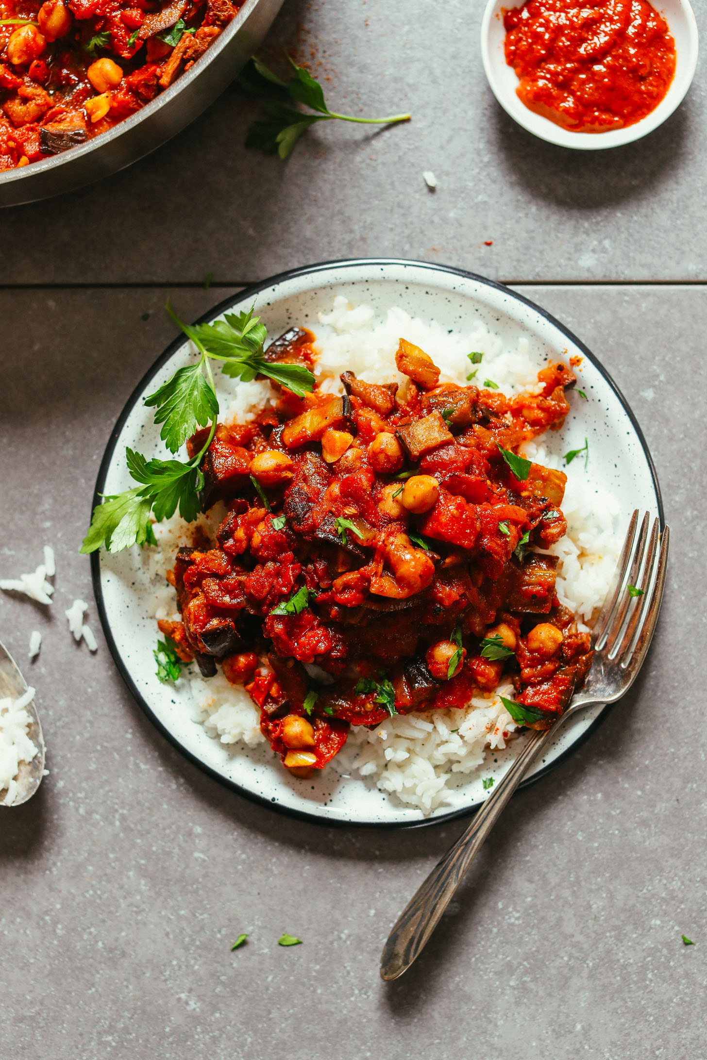 Plate of rice topped with vegan Moroccan-Spiced Roasted Eggplant & Tomato Stew
