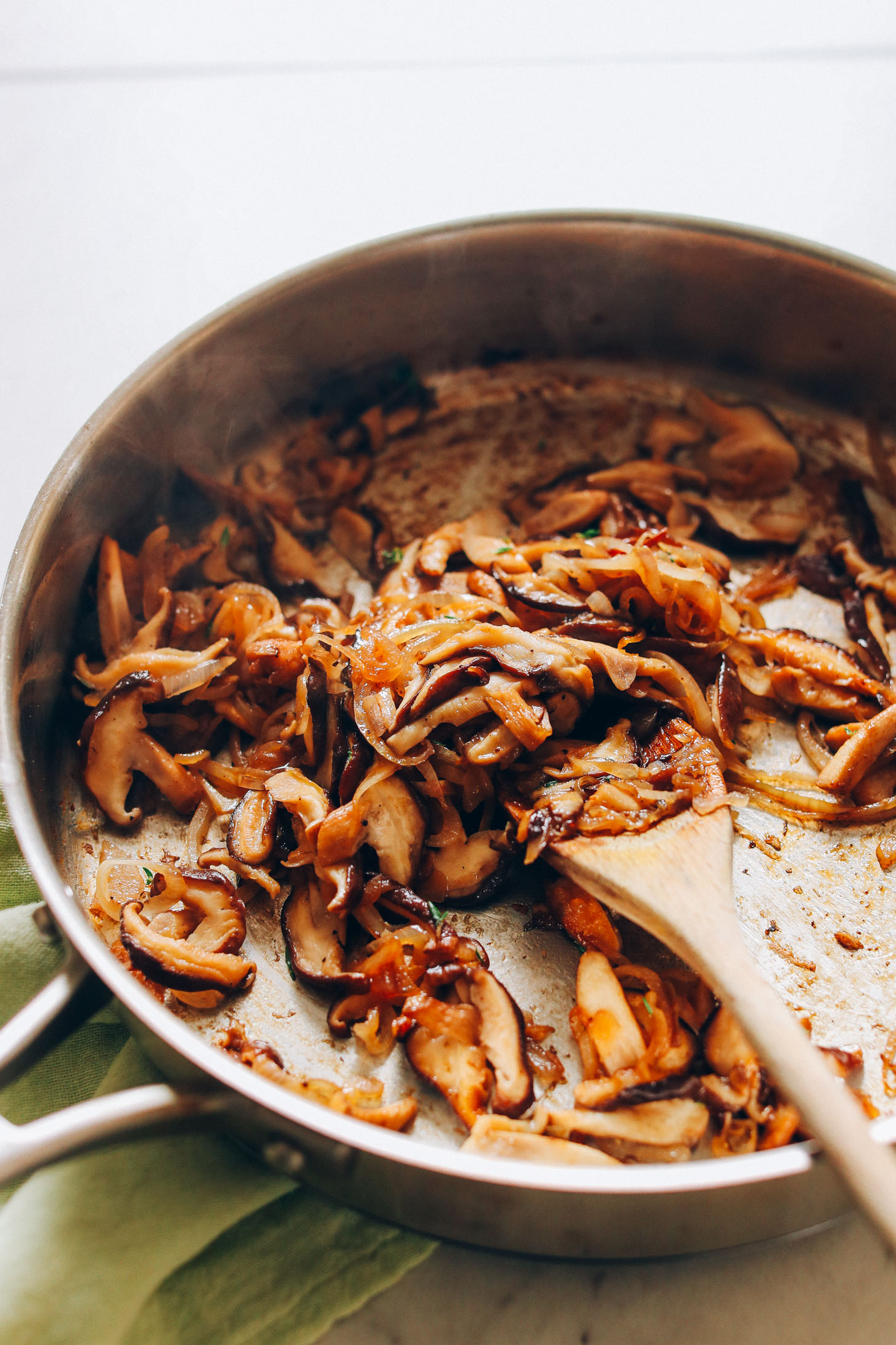 Skillet filled with Caramelized Shiitake Mushrooms and onions for homemade vegan risotto