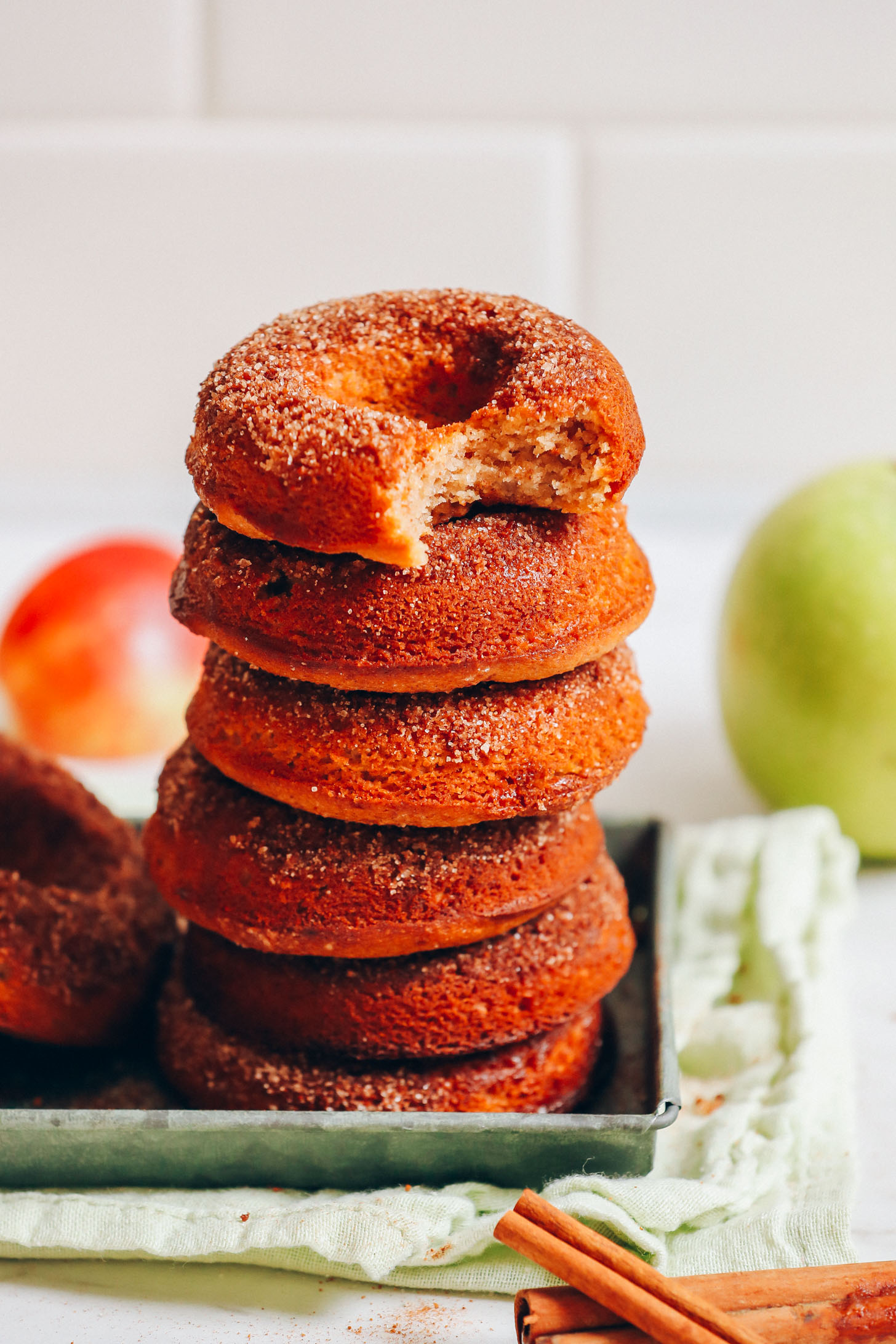 Stack of delicious Vegan Gluten-Free Apple Cider Donuts resting on a metal tray