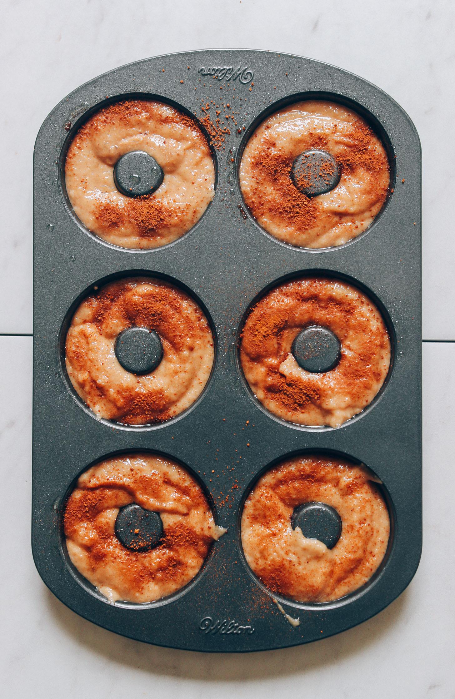 Vegan Gluten-Free Apple Cider donut batter sprinkled with cinnamon in a donut pan