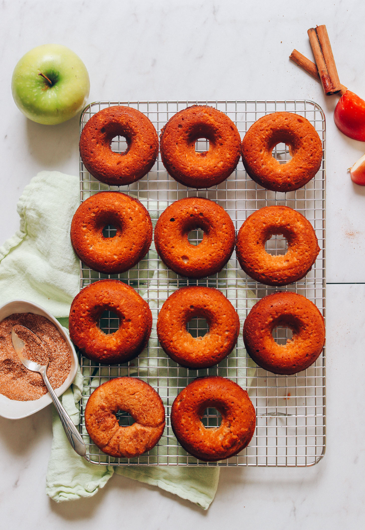 Freshly baked Vegan Gluten-Free Apple Cider Donuts resting on a cooling rack