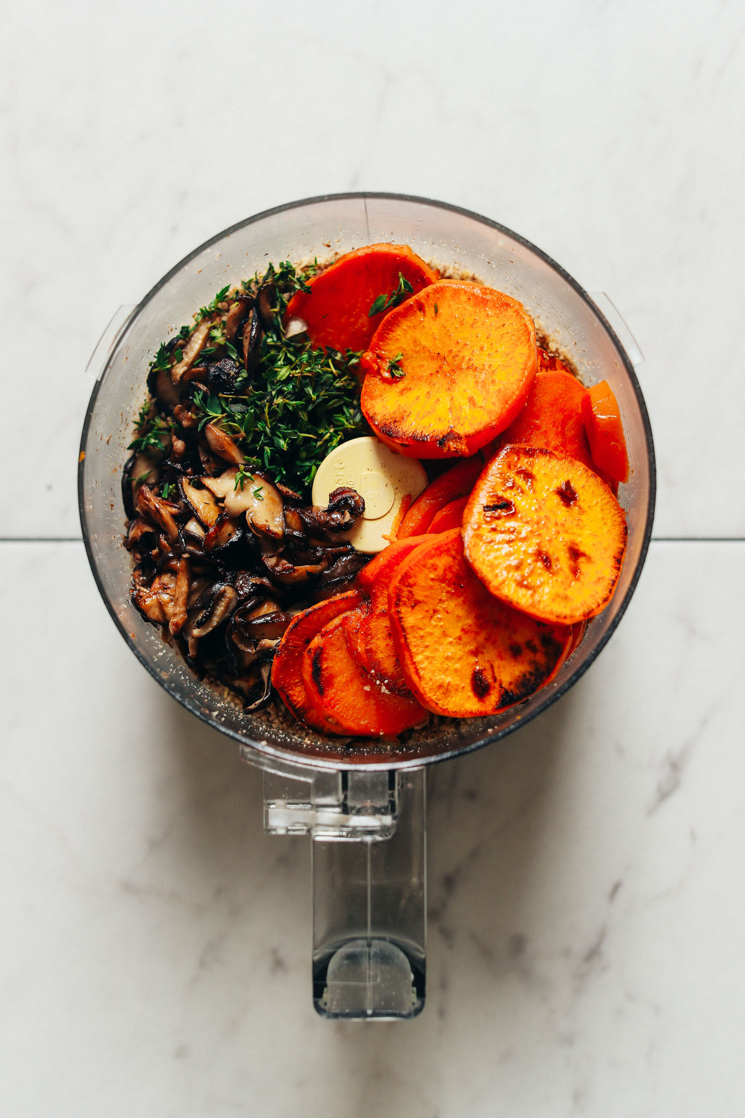Food processor with mushrooms, sweet potatoes, and other ingredients for making Vegan Holiday Meatloaf