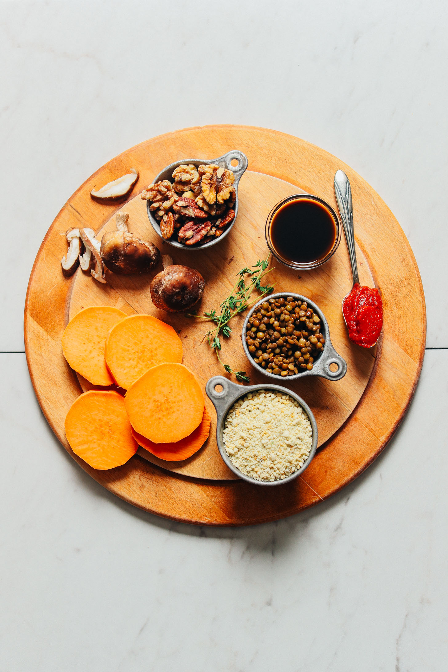 Wood cutting board filled with lentils, sweet potatoes, and other ingredients for making vegan meatloaf