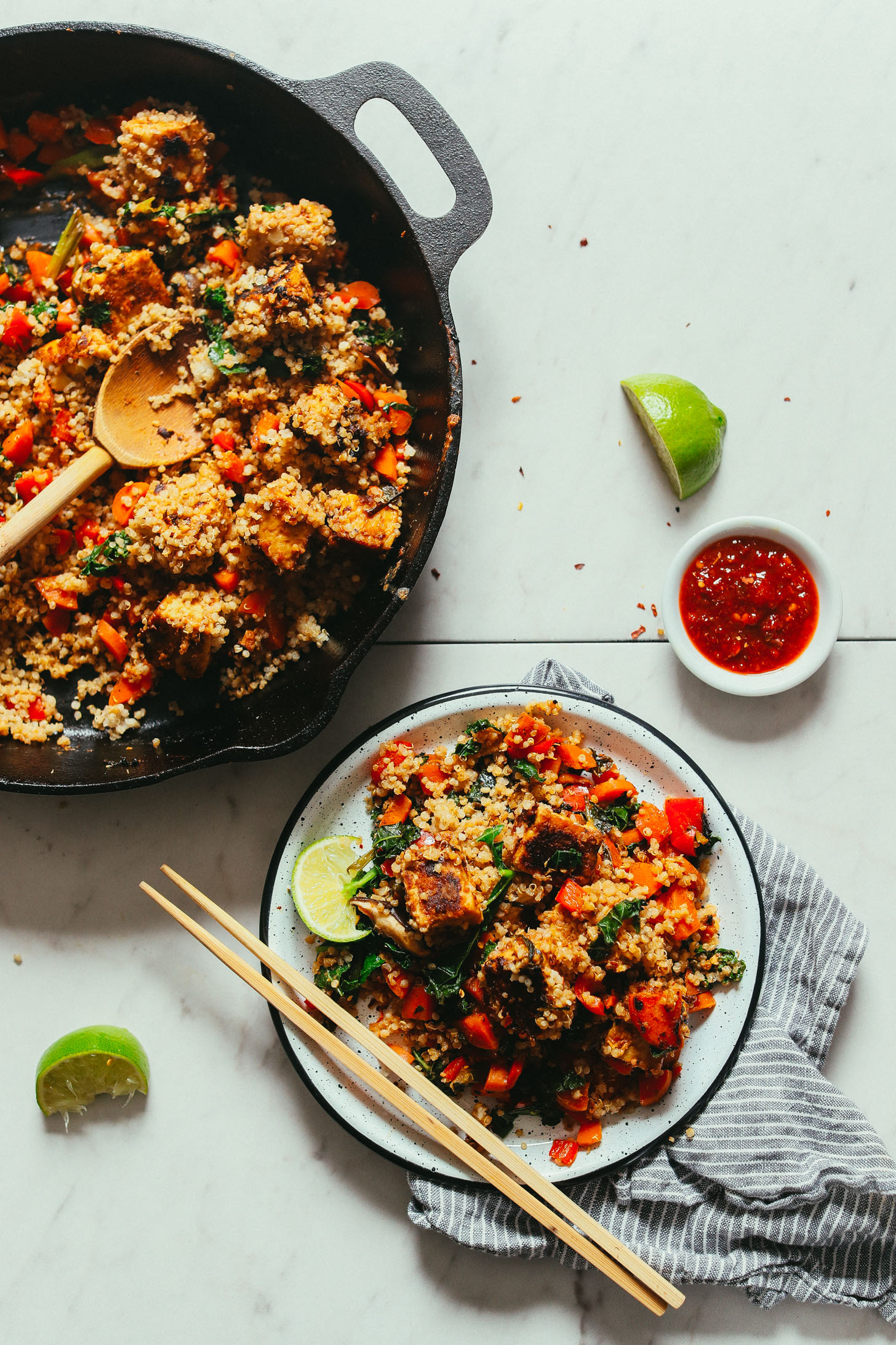 Overhead image of tempeh quinoa stir fry in a cast iron pot with a small serving plate and chopsticks on the side