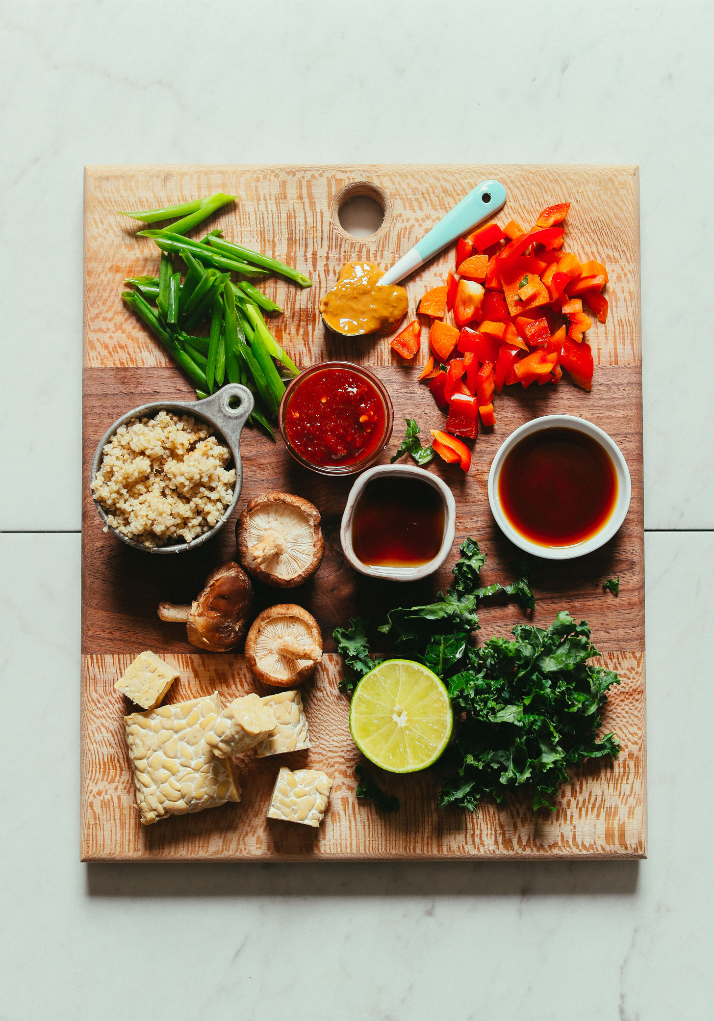 Overhead image of cutting board with ingredients for a tempeh stir fry including tempeh quinoa bell pepper green onion and kale