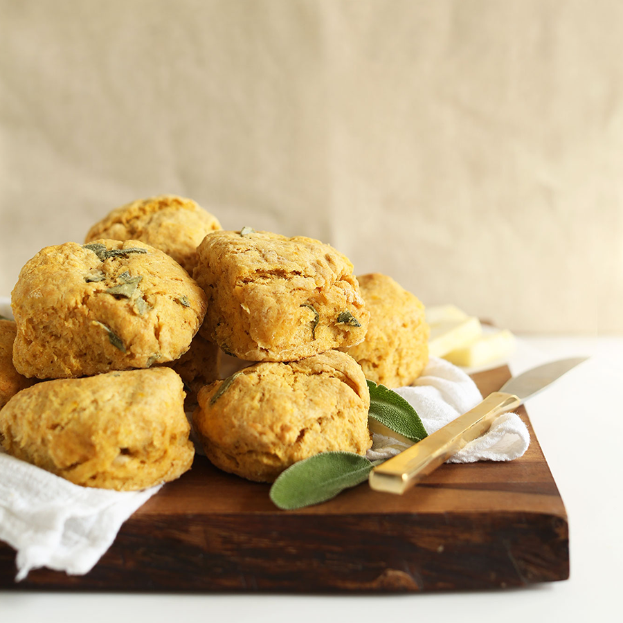 Cutting board with a batch of Pumpkin Sage Biscuits on a white linen