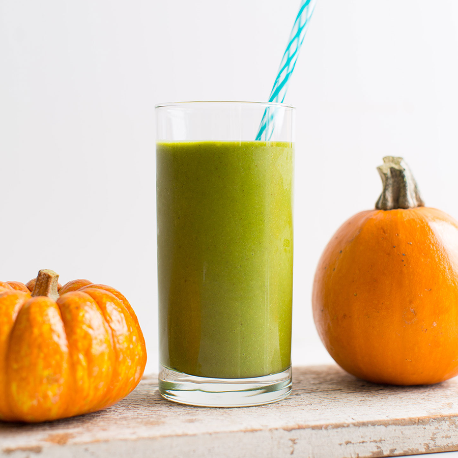 Tall glass of our Pumpkin Green Smoothie recipe between two pumpkins