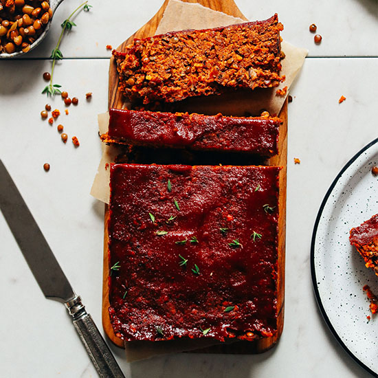 Vegan Lentil Meatloaf partially sliced on a cutting board