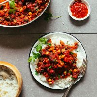 Plate of Moroccan Eggplant Tomato Stew with fresh parsley served over white rice