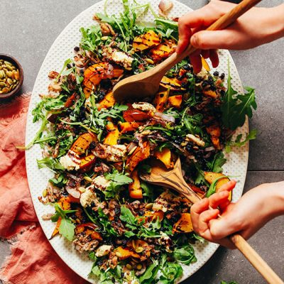 Using salad tongs to grab a scoop of Roasted Squash Salad with Nut Cheese and Balsamic Reduction