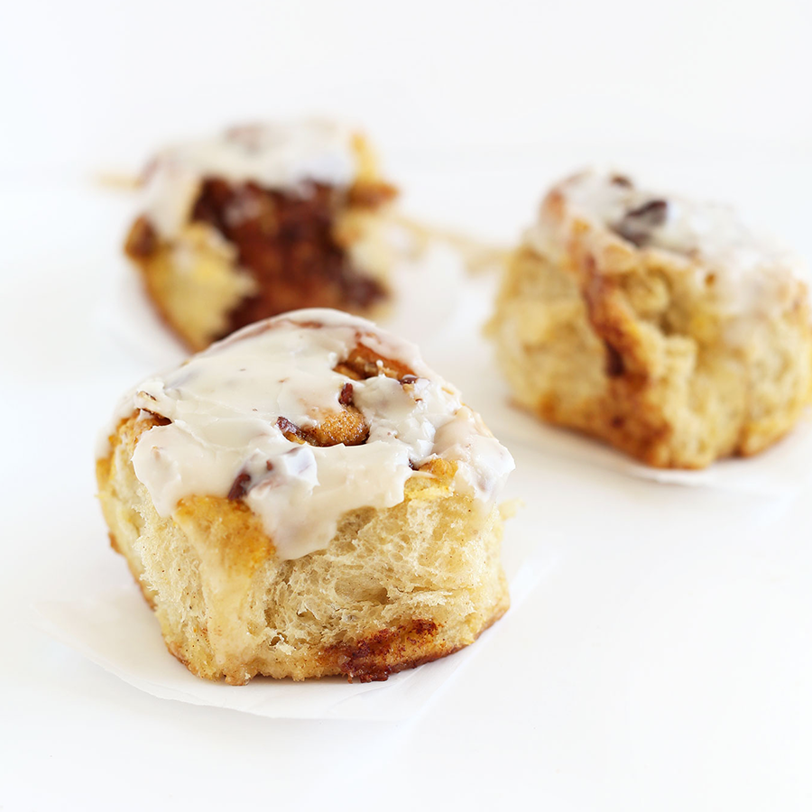 Three iced Pumpkin Cinnamon Rolls on squares of parchment paper