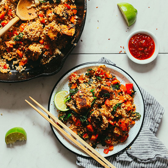 Plate and skillet of Tempeh Veggie Stir Fry with chili sauce and fresh limes