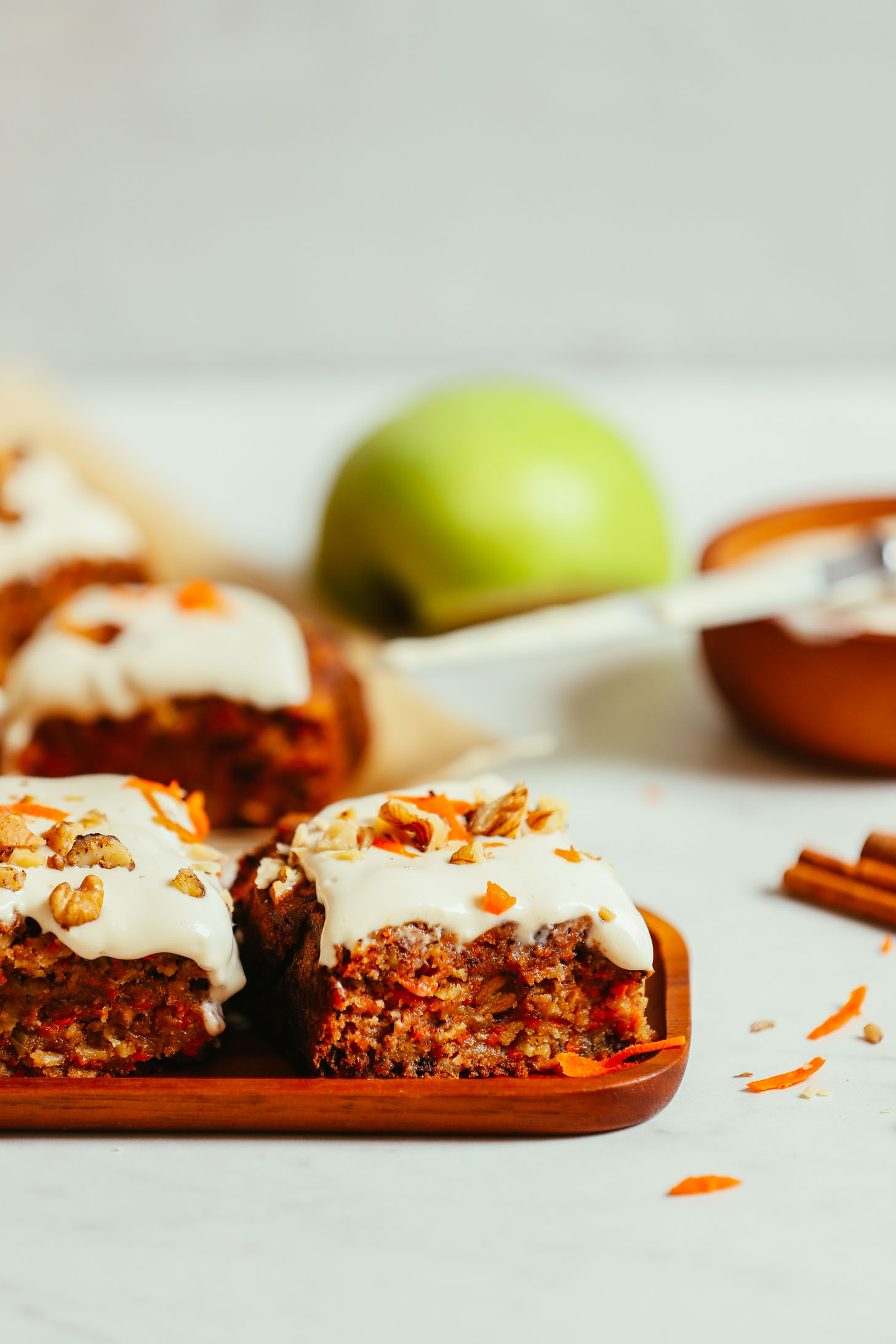 Wood tray and parchment paper with slices of gluten-free vegan Carrot Apple Snack Cake