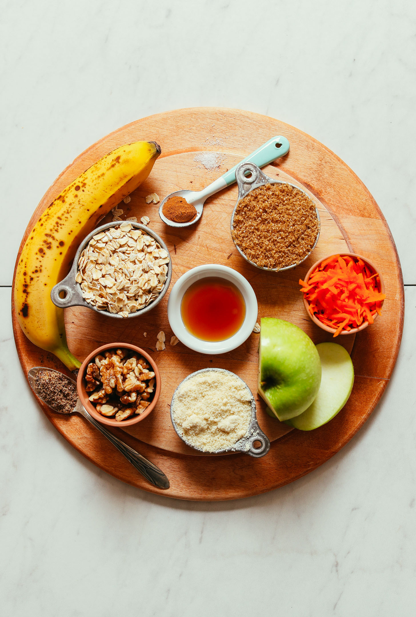 Wood cutting board with ingredients for making Carrot Apple Snack Cake