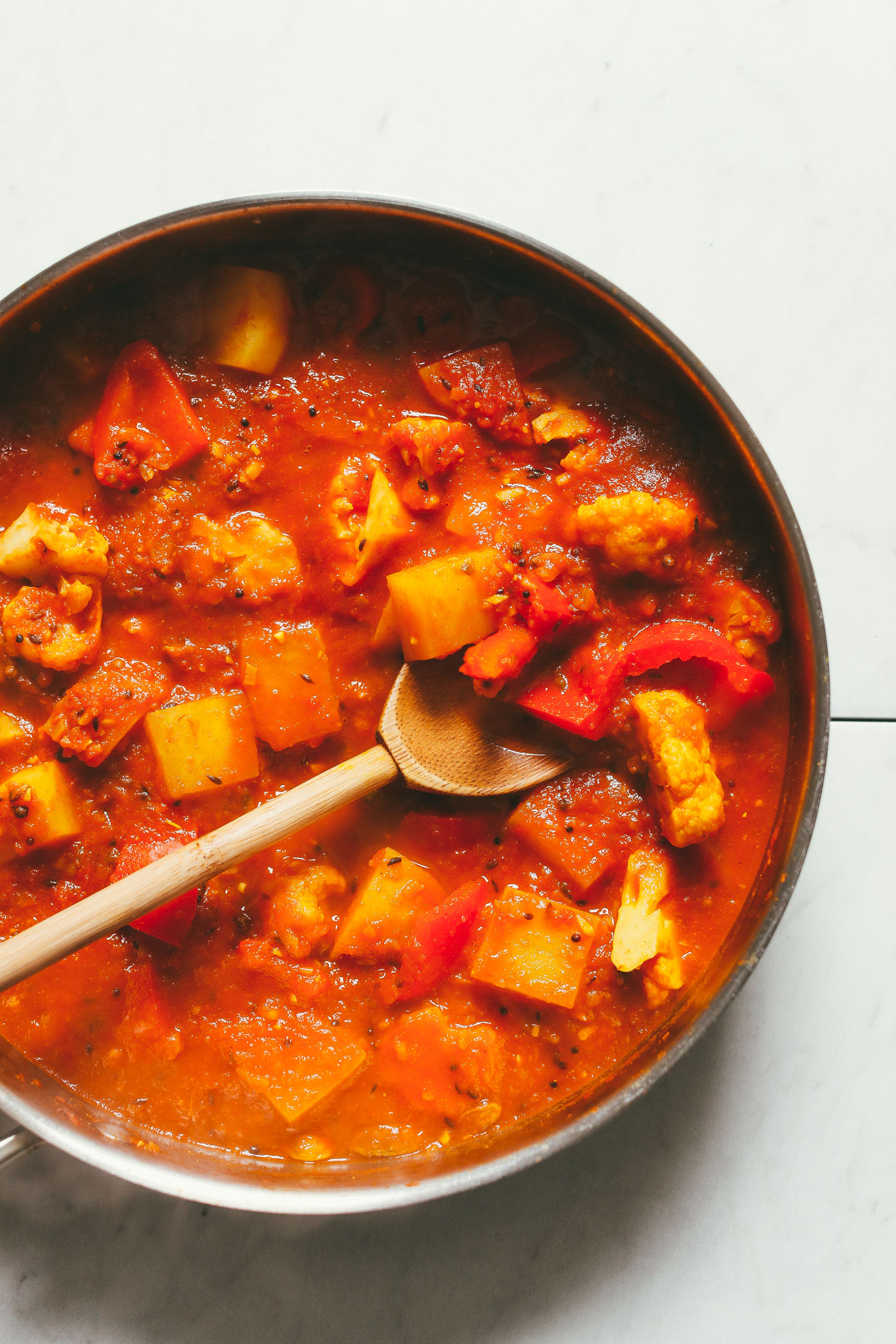 An overhead image of a pan with red lentil curry, potatoes, red bell pepper, and cauliflower being stirred with a wooden spoon