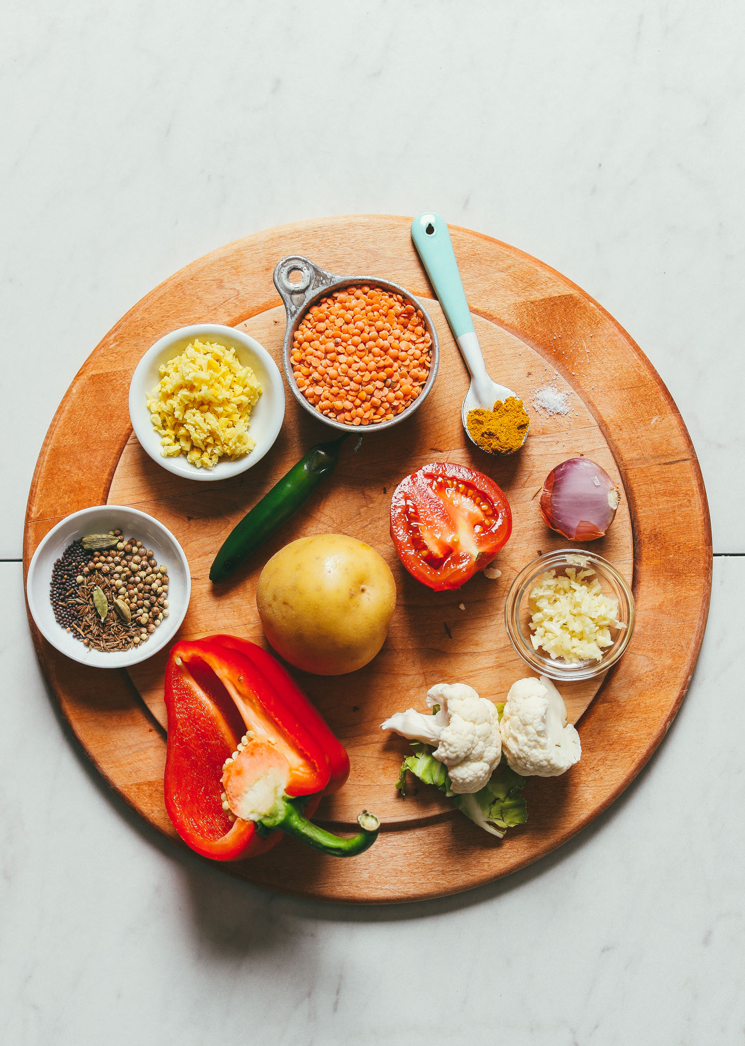 Ingredients for red lentil curry with potato, red bell pepper, and cauliflower on a cutting board