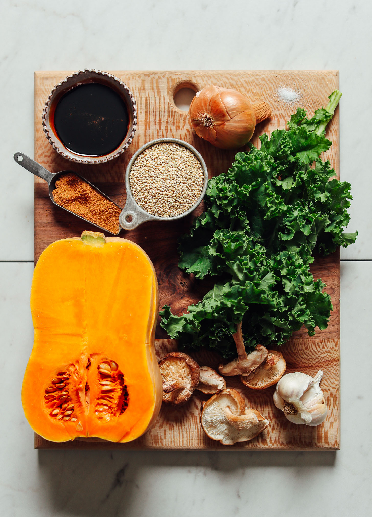 Cutting board with ingredients for making holiday stuffed butternut squash