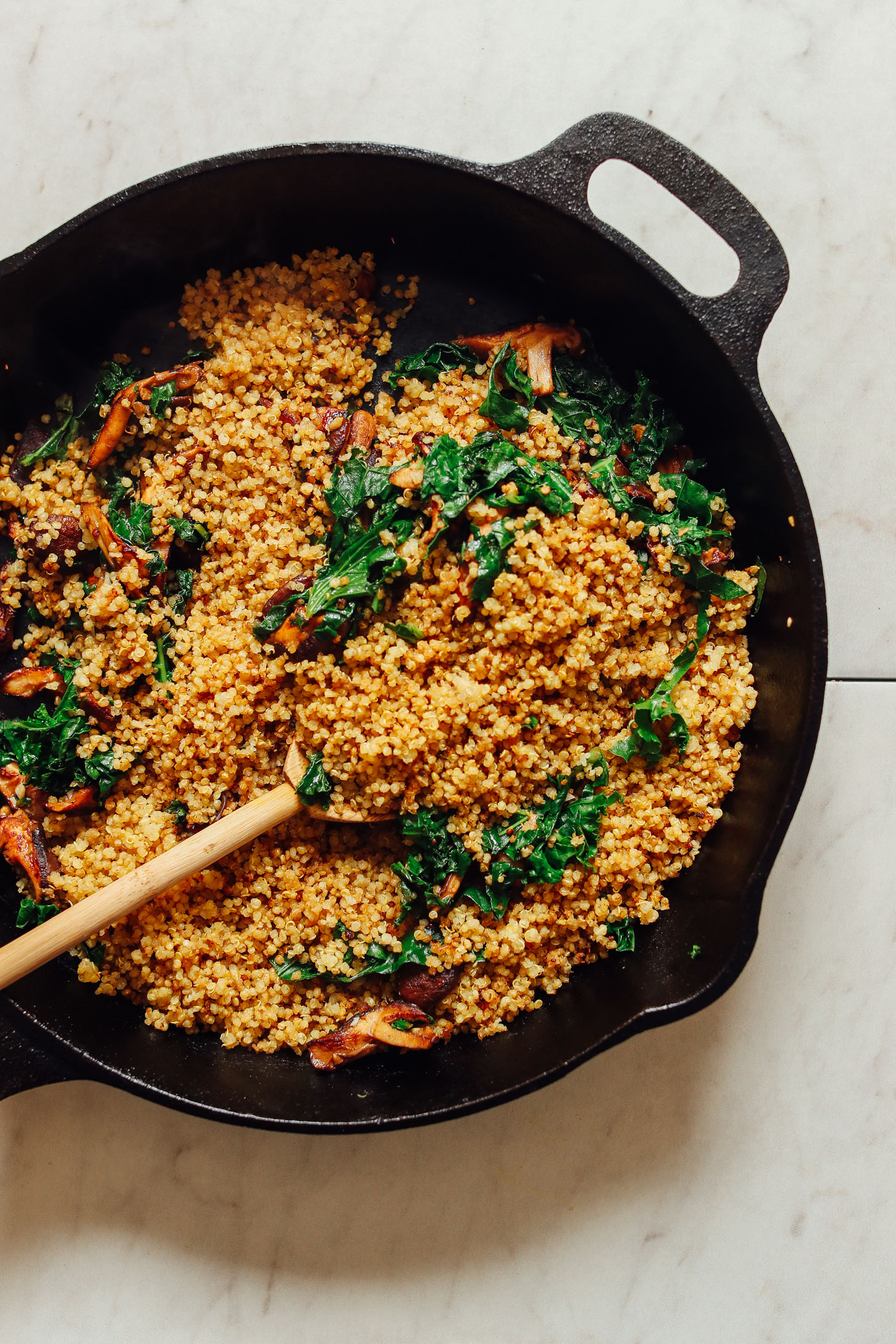 Cooking quinoa, mushrooms, and kale in a cast-iron skillet for our vegan stuffed butternut squash recipe