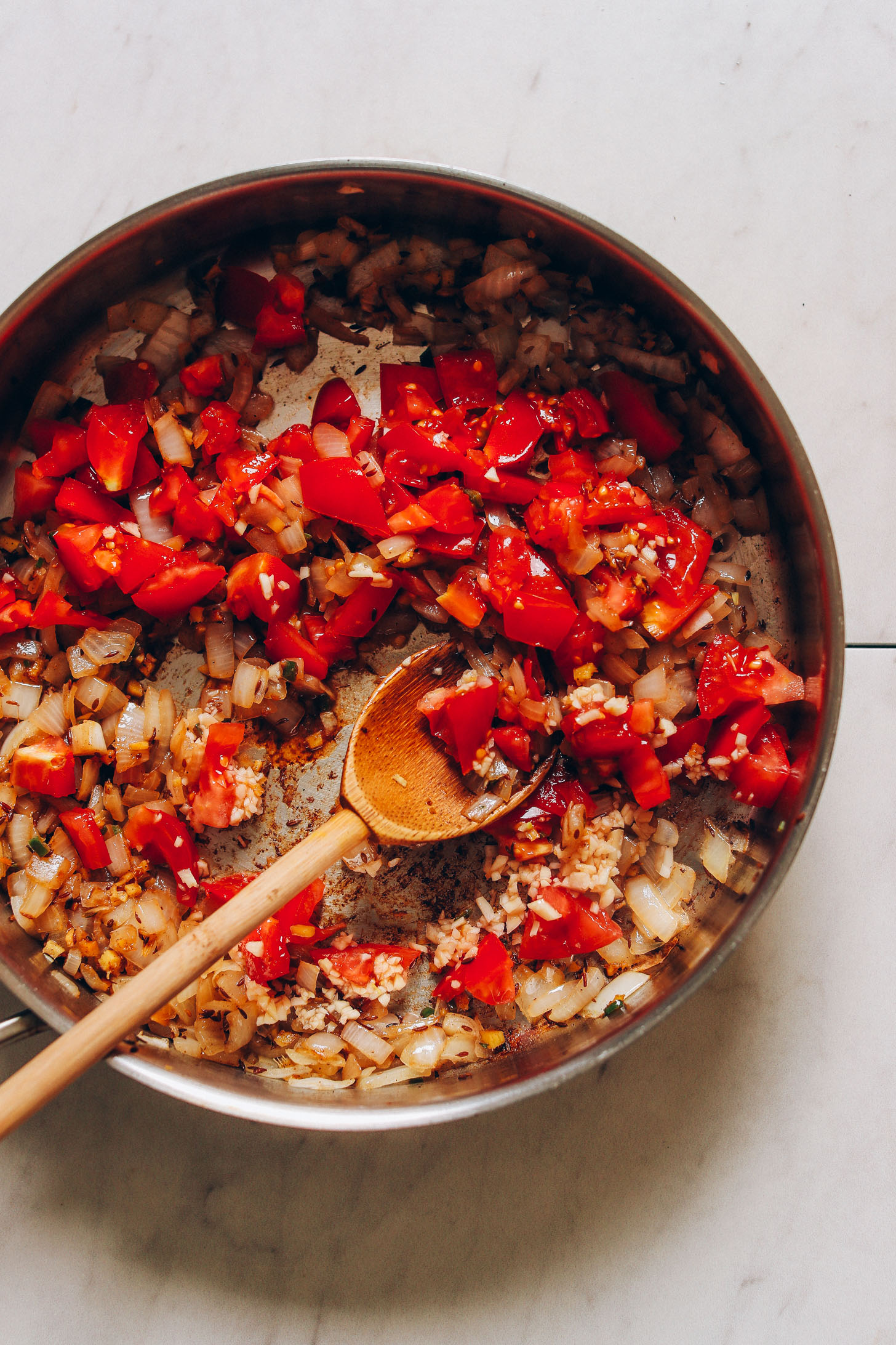 Overhead image of tomatoes, onion, and garlic being sautéed in a skillet with a wooden spoon stirring the ingredients