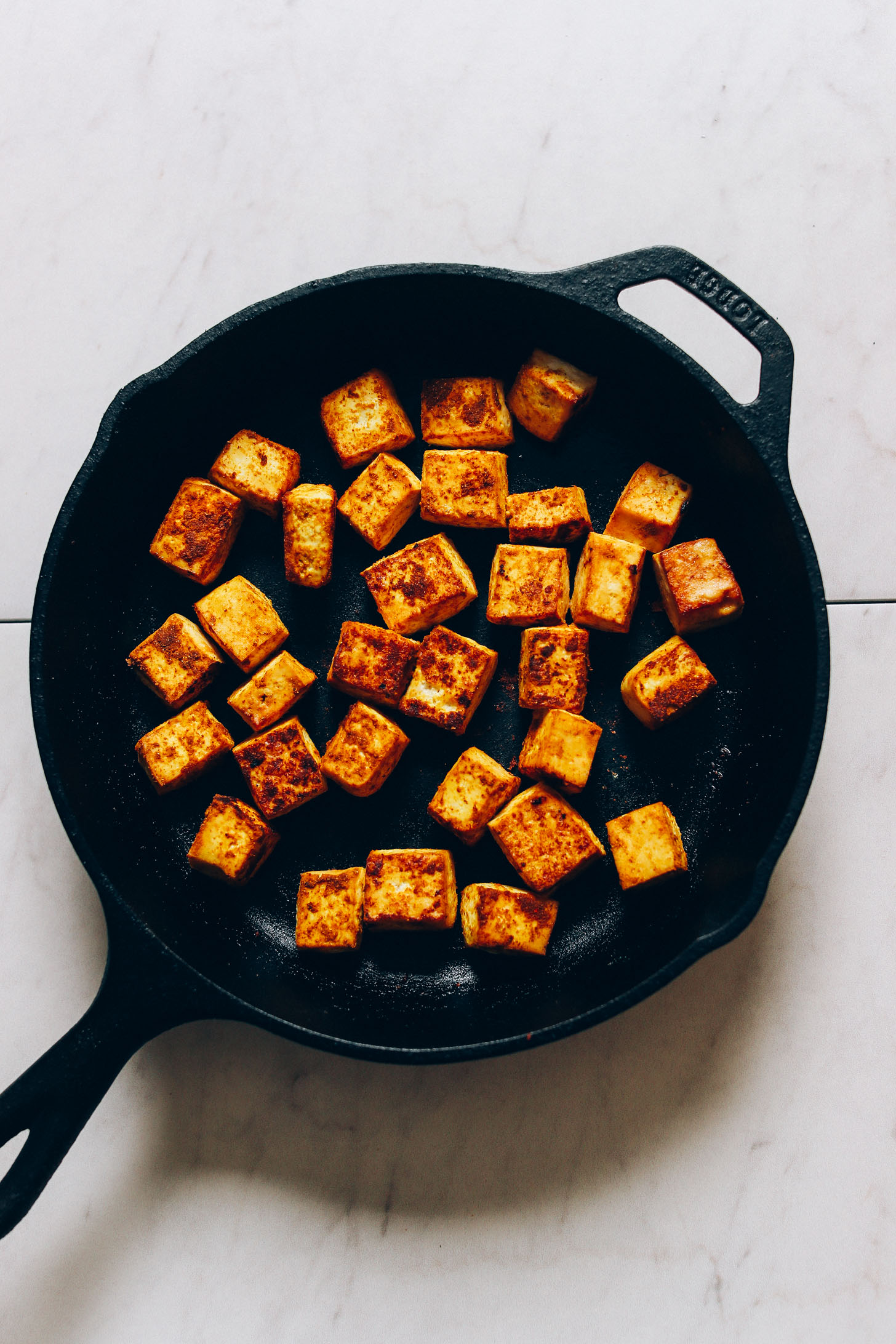 Overhead image of tofu being browned in a cast iron skillet with curry spices