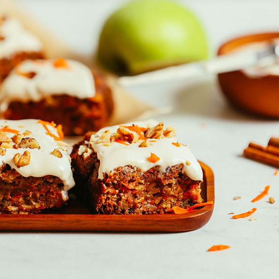Slices of Carrot Apple Snack Cake on a platter and parchment paper