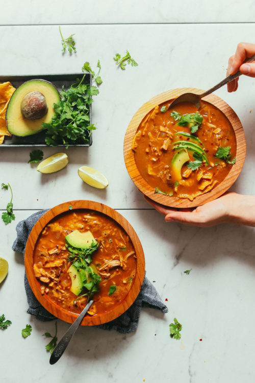 Wood serving bowls filled delicious Vegan Tortilla Soup made with jackfruit
