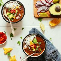 Bowls of our delicious 1-Pot Black Bean Soup topped with avocado, tortilla chips, and avocado