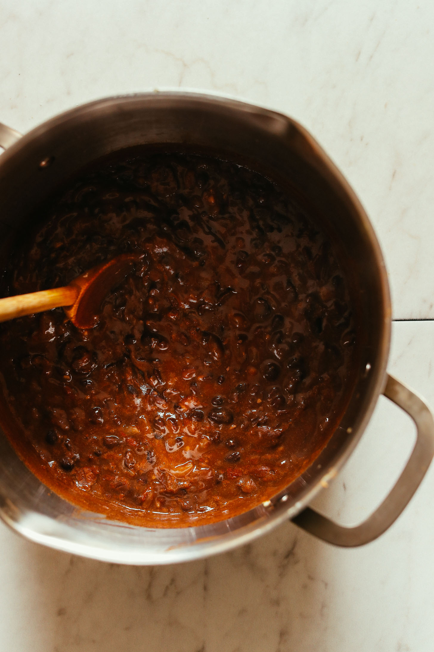 Overhead image of pot with black bean soup and a wooden spoon stirring the ingredients