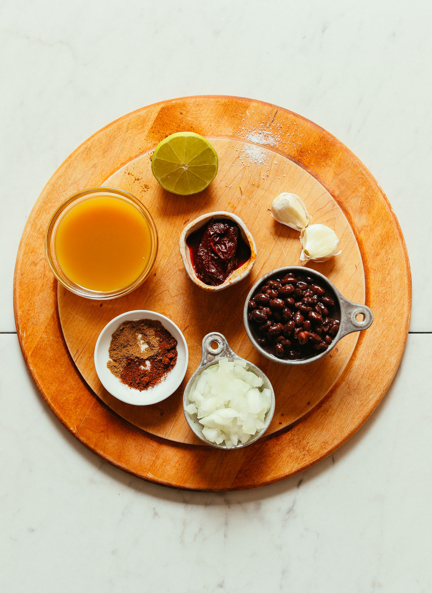 Overhead image of cutting board holding ingredients for black bean soup, including black beans, onion, lime, and vegetable broth