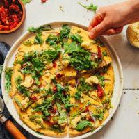 Grabbing a slice of gluten-free Socca Pizza made with Vegan Pesto