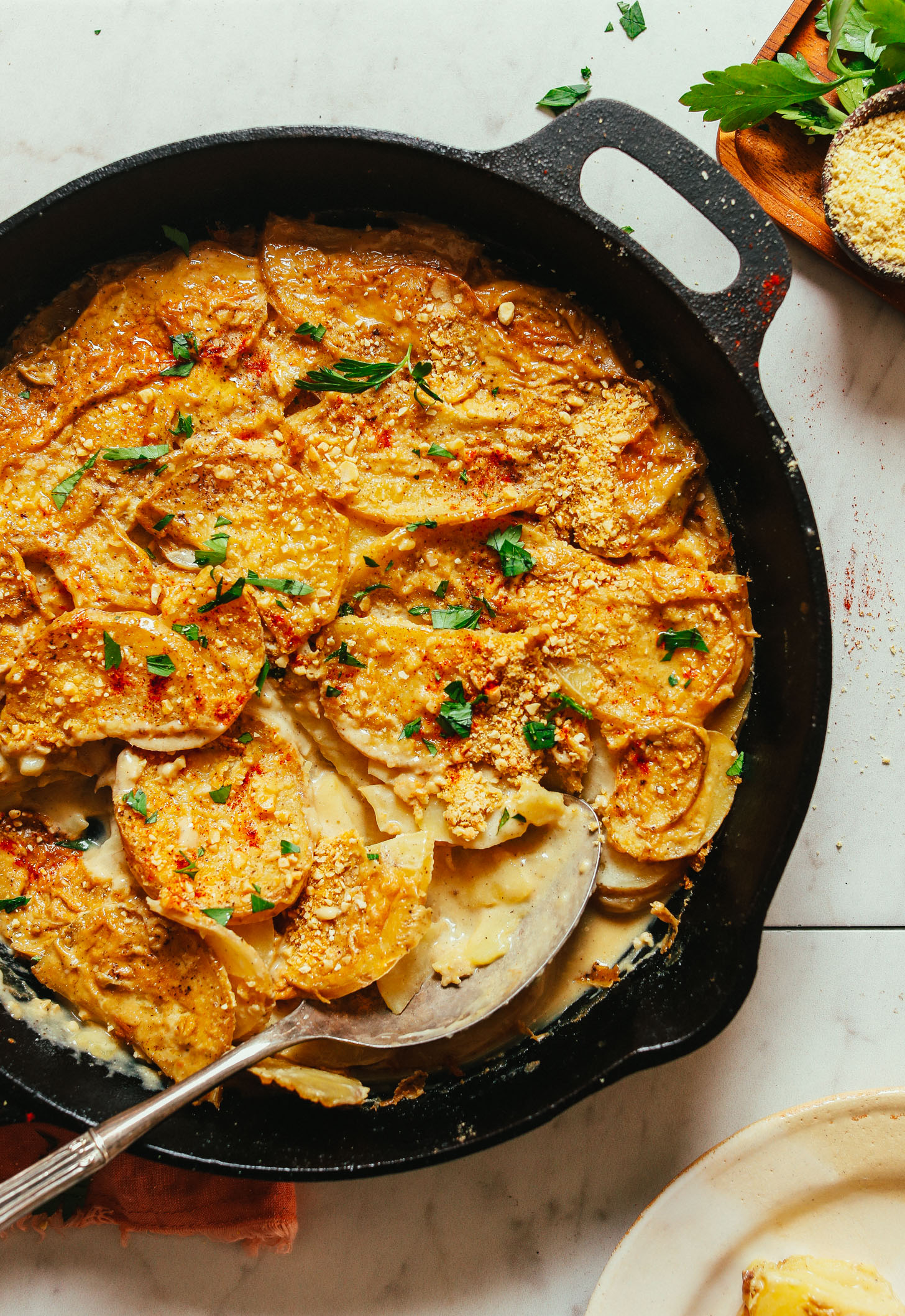 Cast-iron skillet filled with a batch of easy Vegan Scalloped Potatoes