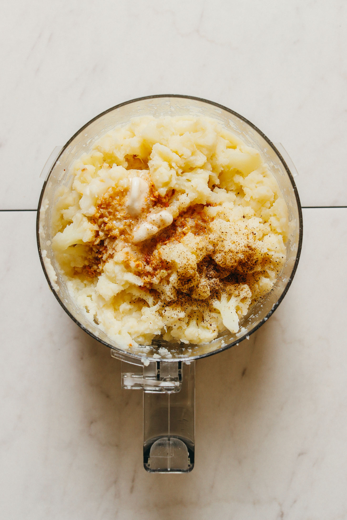 Food processor with mashed cauliflower, spices, and vegan butter for a delicious vegan Thanksgiving side recipe