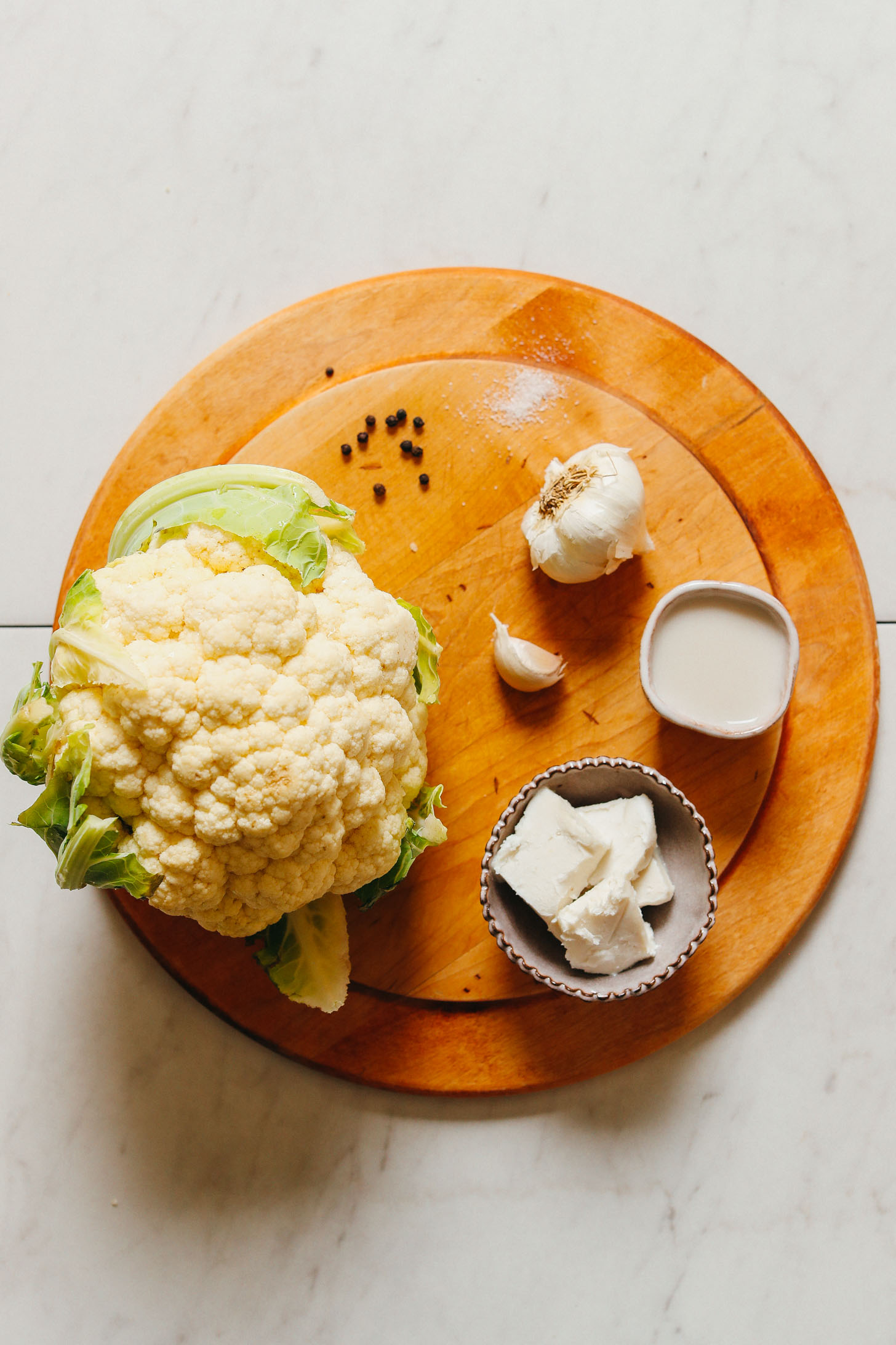 """Cutting board with cauliflower, garlic, and other ingredients for making vegan Cauliflower Mashed """"Potatoes"""""""