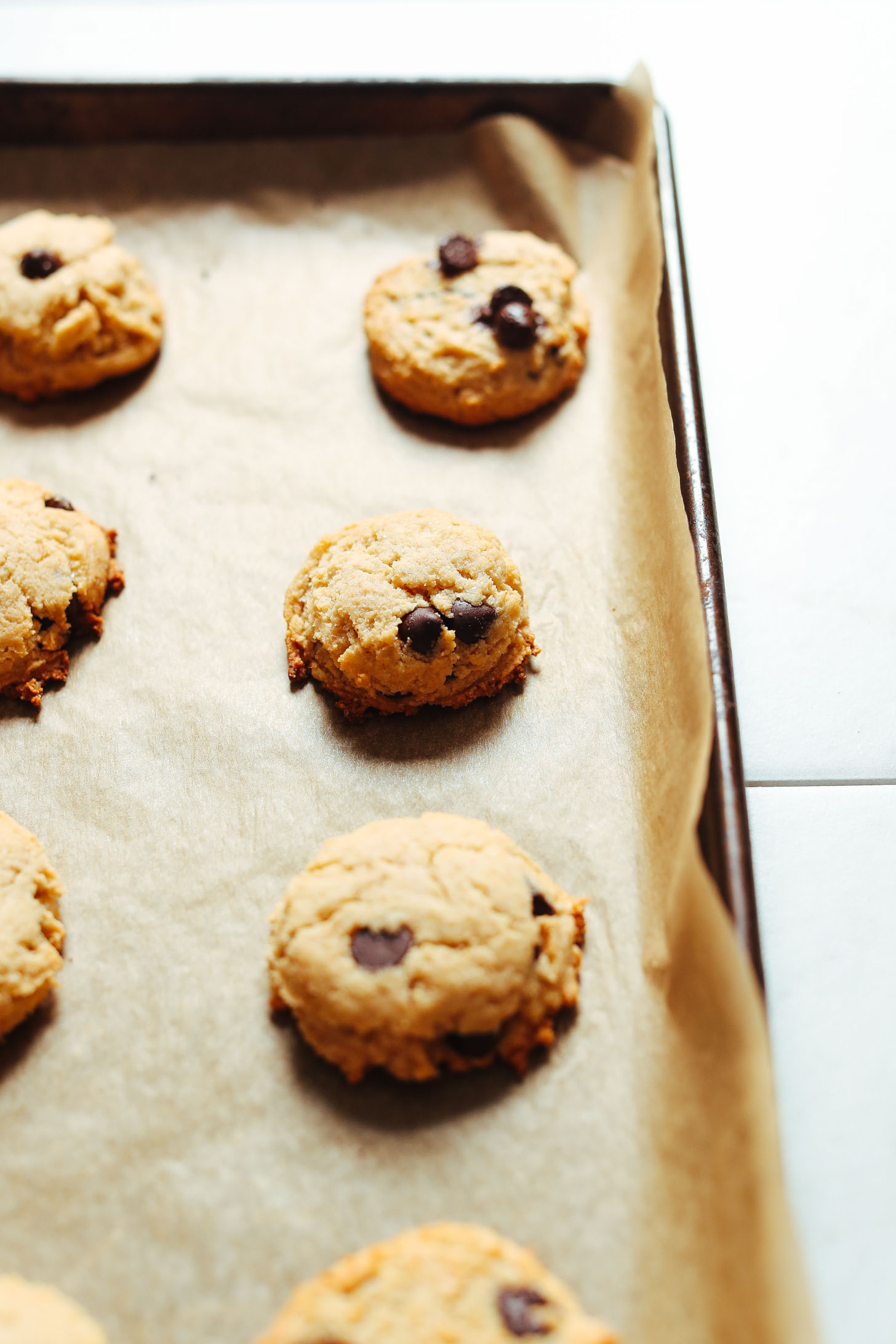 Parchment-lined baking sheet with a batch of Vegan Gluten-Free Chocolate Chip Cookies