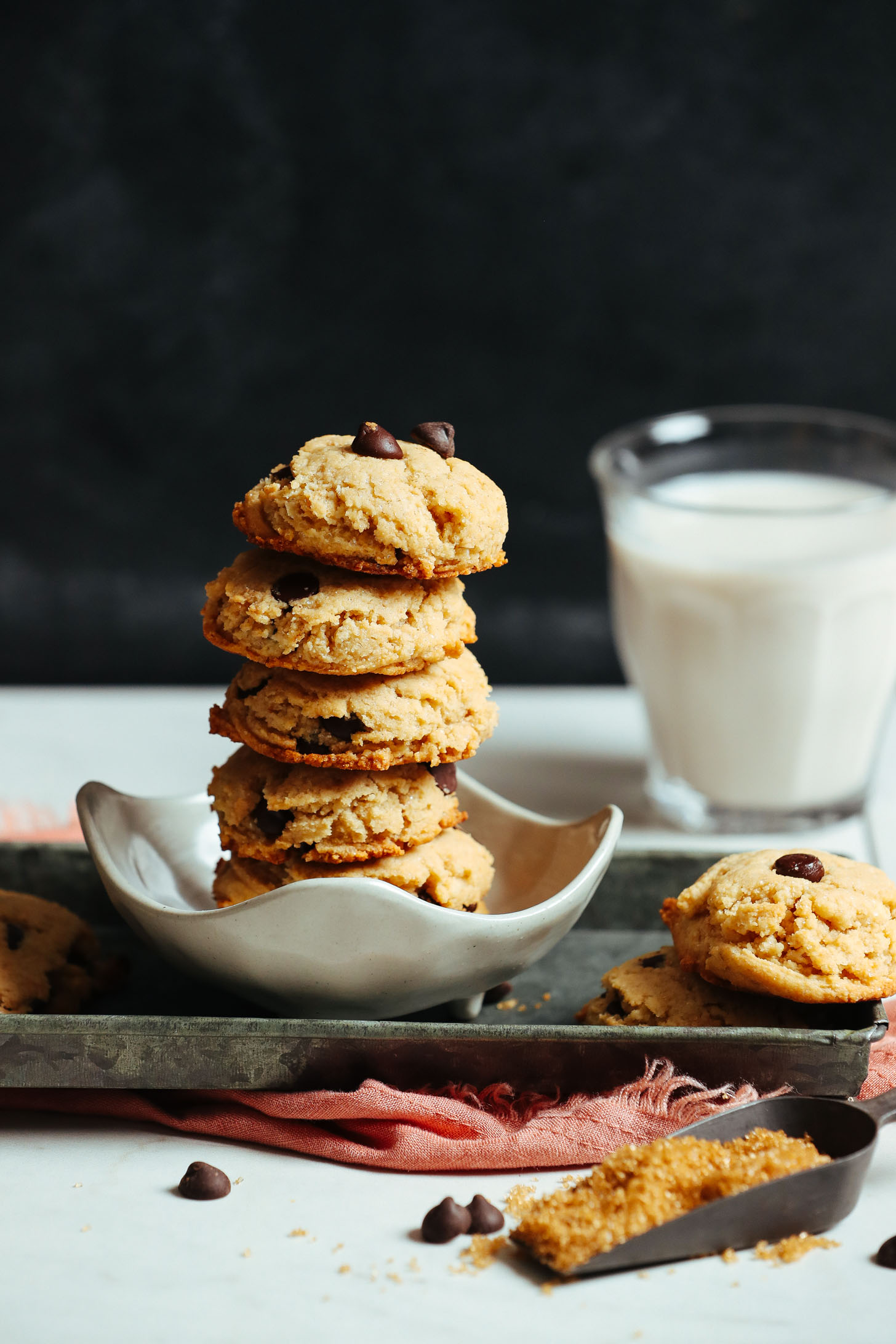 Stack of delicious gluten-free vegan chocolate chip cookies beside a glass of almond milk