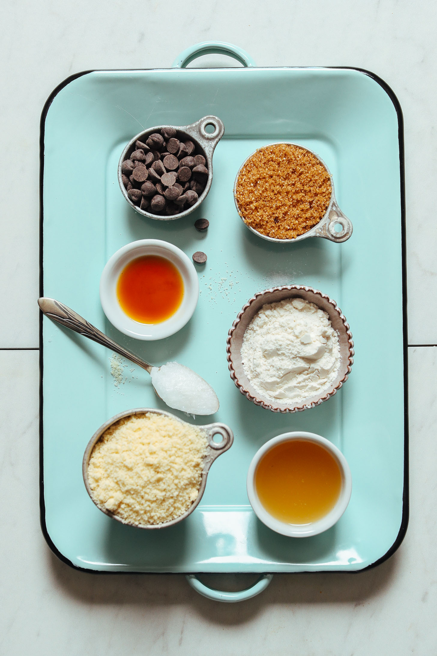 Blue tray displaying almond flour and other ingredients for making vegan gluten-free chocolate chip cookies