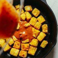 Pouring peanut sauce into a skillet of Crispy Peanut Tofu