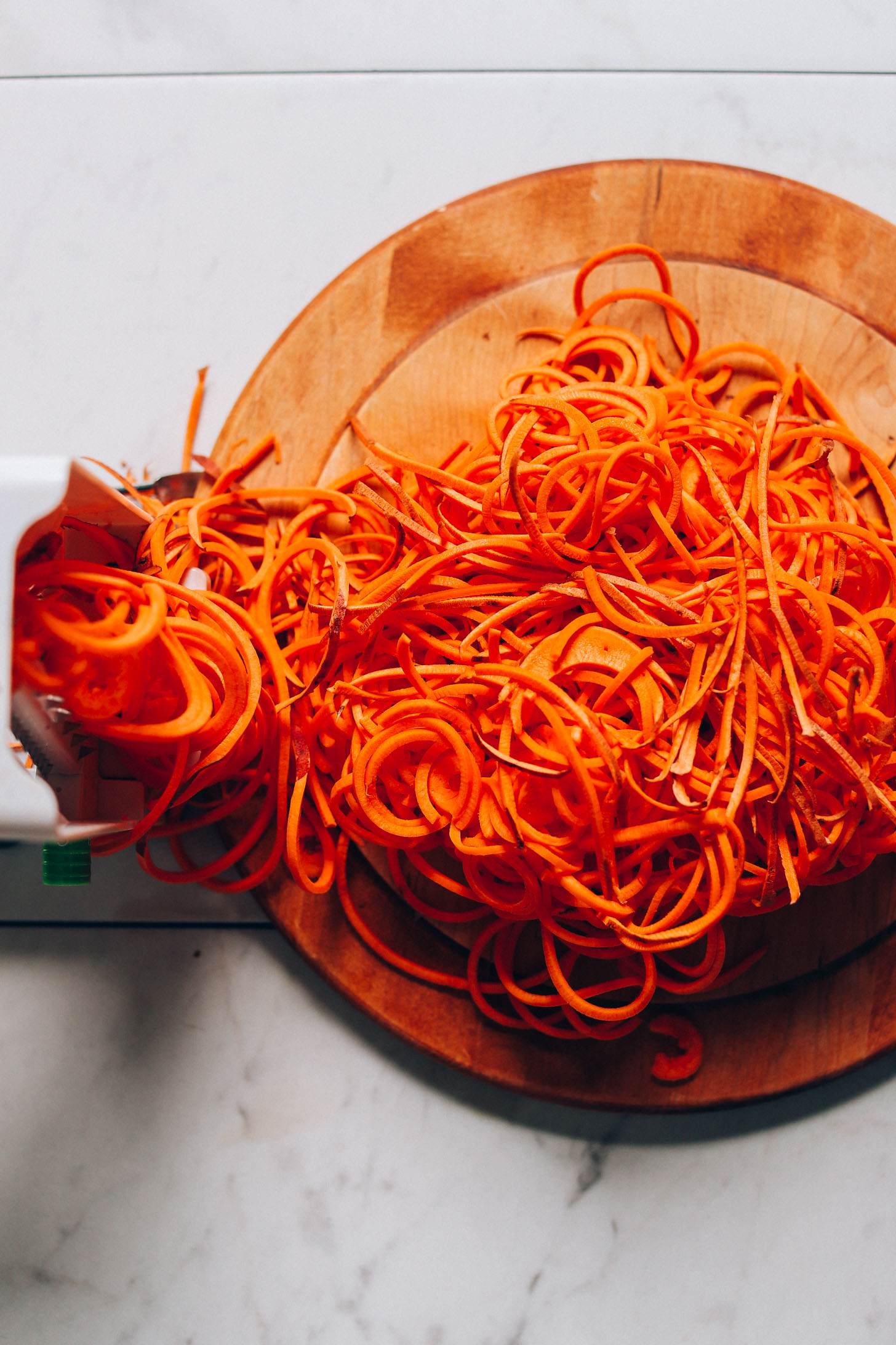 Cutting board with spiralized sweet potatoes for making Sweet Potato Hashbrowns