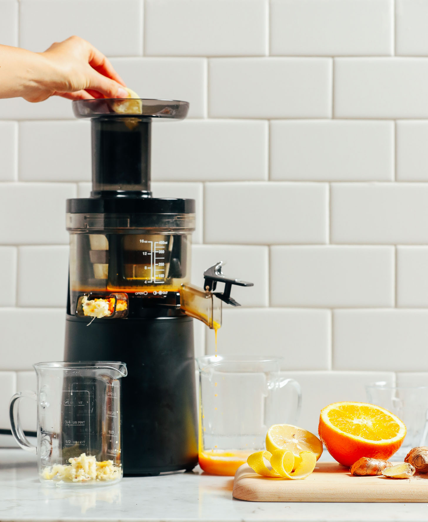 Showing how to use a juicer to make Turmeric Wellness Shots