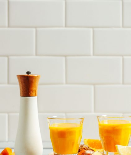 Glasses of our 5-Ingredient Turmeric Wellness Shots recipe surrounded by ingredients used to make them