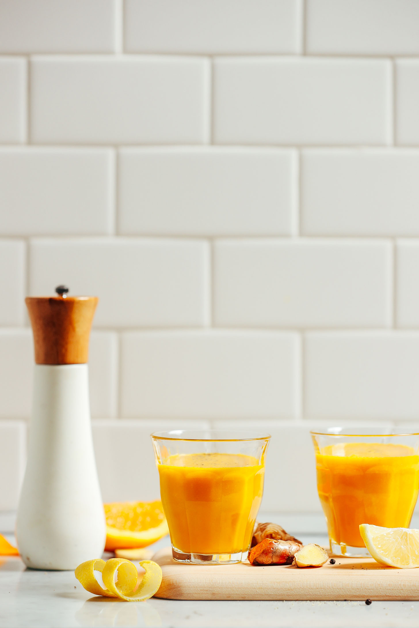 Two glasses of Turmeric Wellness Shots for an anti-inflammatory homemade juice