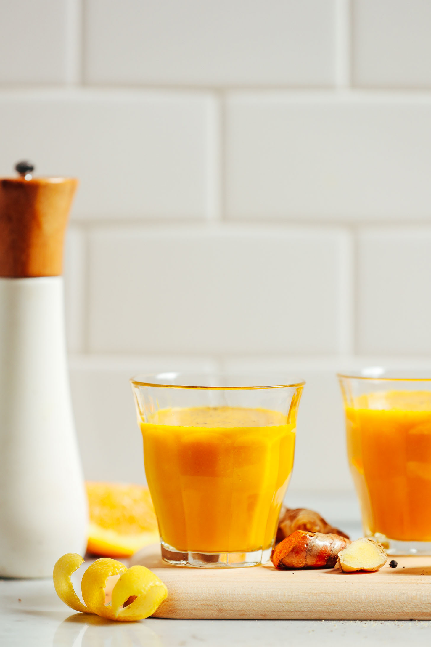 Turmeric Wellness Shots on a cutting board ready to drink for a healthy boost