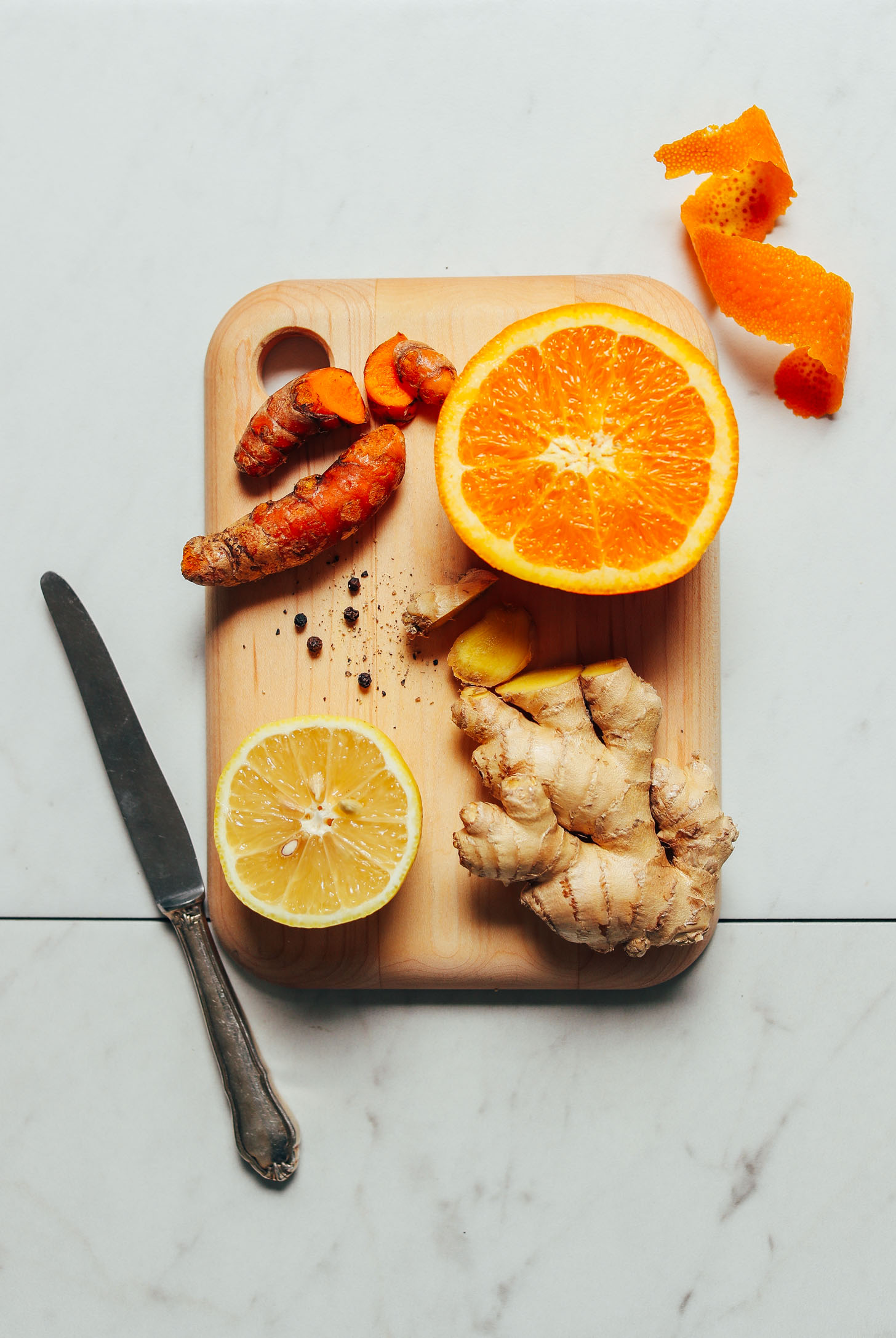 Fresh orange, turmeric, ginger, lemon and black pepper for making homemade wellness shots