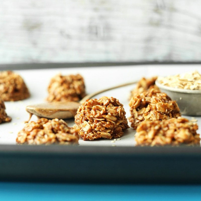 Spoonful of almond butter and bowl of oats on a baking sheet with Almond Butter No-Bake Cookies