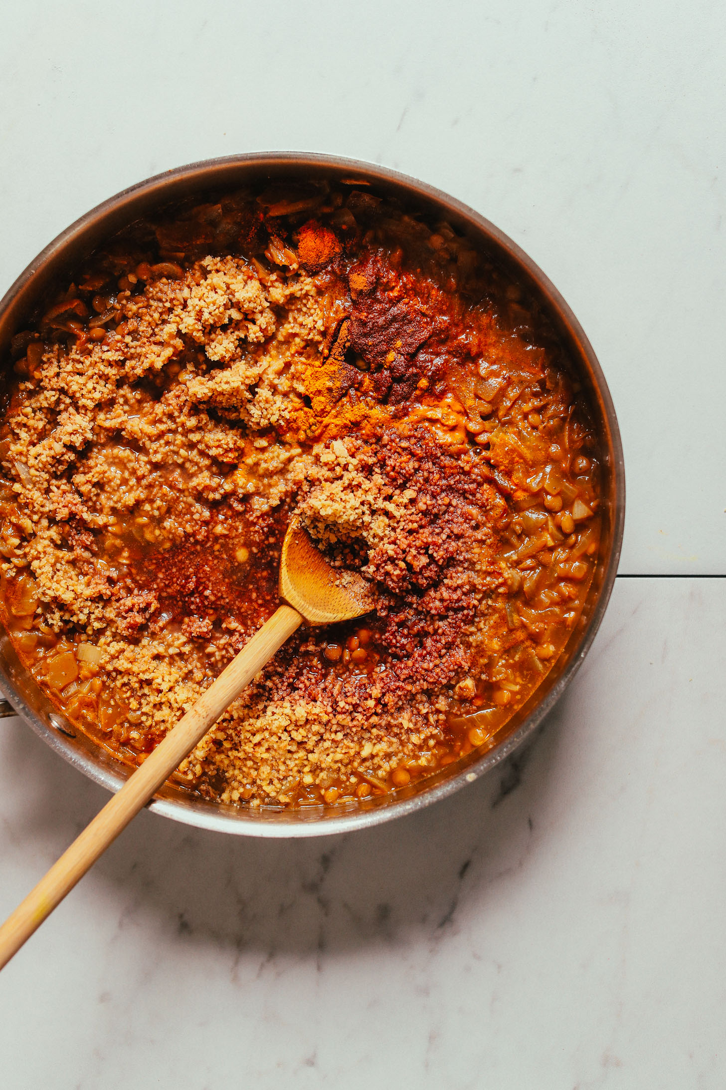 Stirring a skillet of our satisfying vegan Lentil Fesenjan recipe