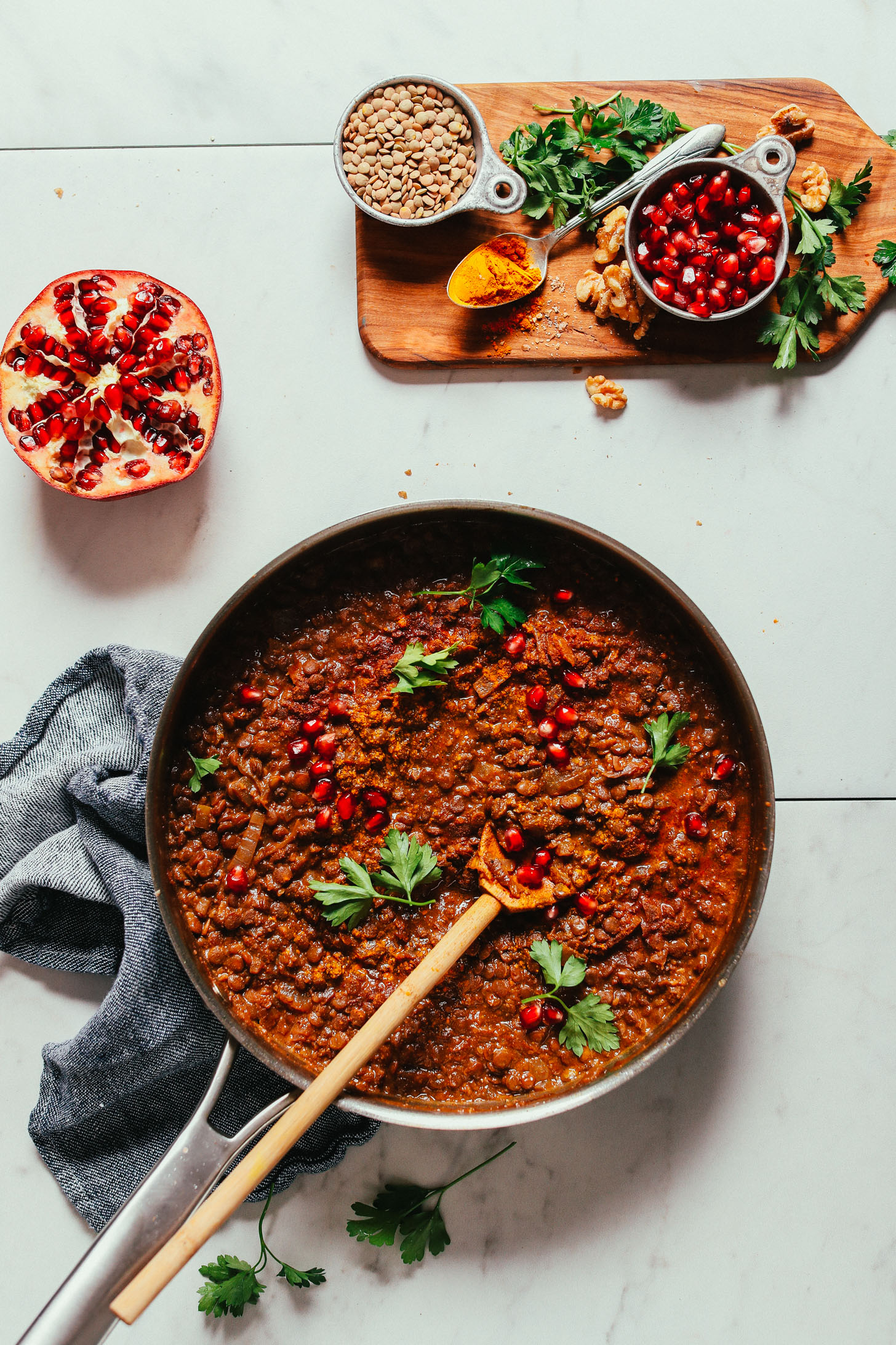 Pan of gluten-free vegan Lentil Fesenjan and a cutting board with ingredients used to make it