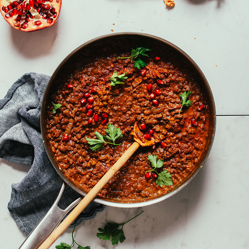 Wooden spoon in a pan of Vegan Lentil Fesenjan topped with pomegranate seeds and parsley